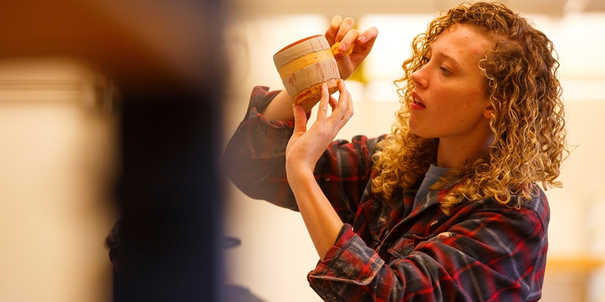 A Northwestern student touches up the glaze work on her pottery piece.
