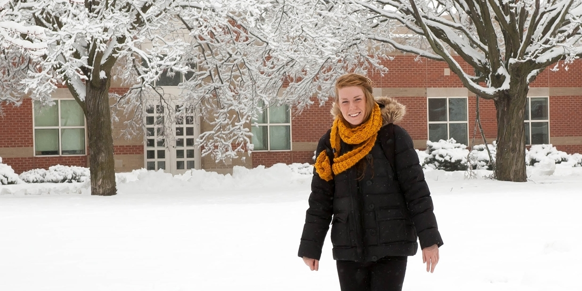 A student walks across a snowy campus.