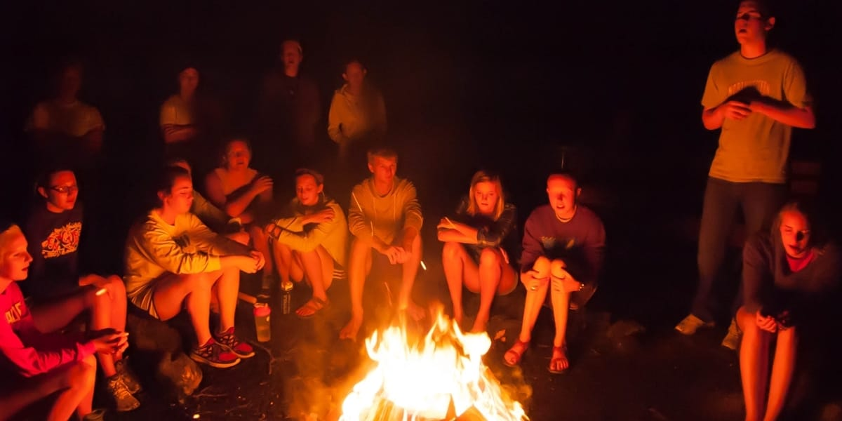 Students huddle around a bonfire during a spiritual retreat.