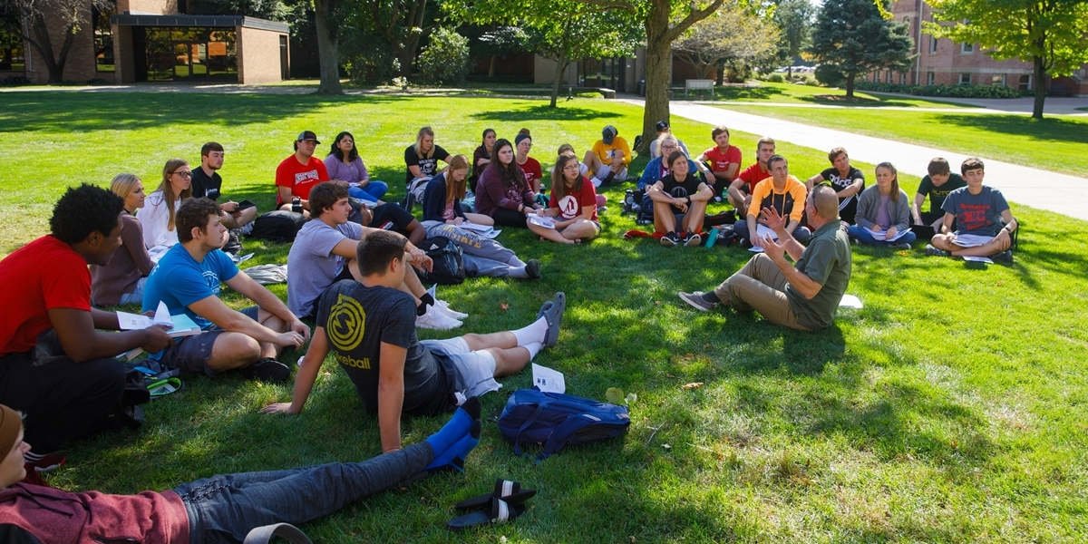 A professor teaches a theology class outside on a pleasant fall day.