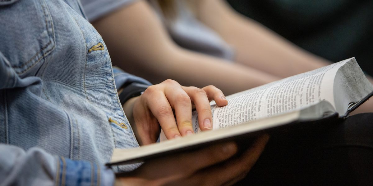 A student reads a Bible during chapel.