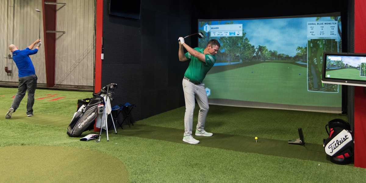 A Northwestern student practices his swing using the golf simulator in the Juffer Athletic Fieldhouse.