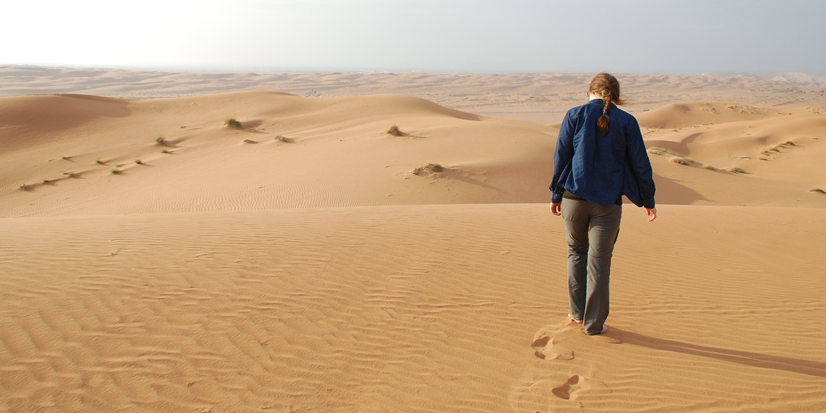 A Northwestern student walks in the desert during her semester in Oman.