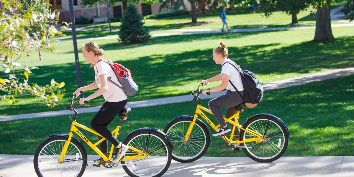 Students ride college-owned bikes on campus.