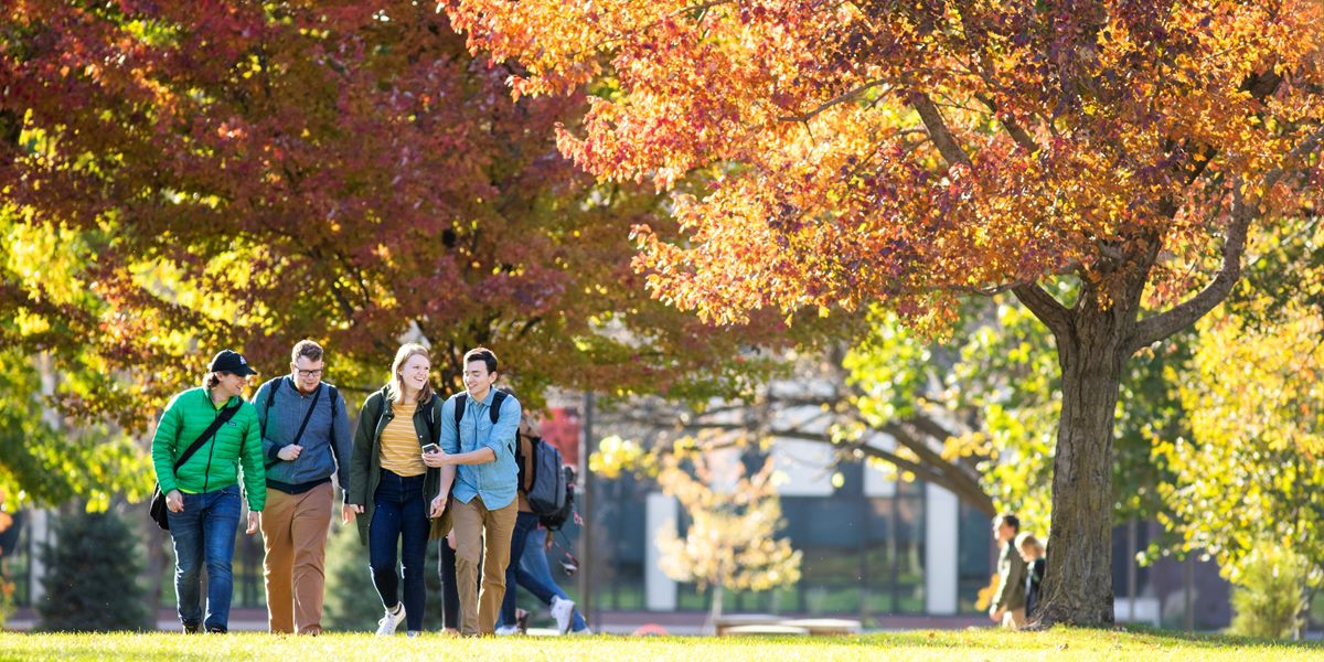 Students walk across campus on an autumn morning.