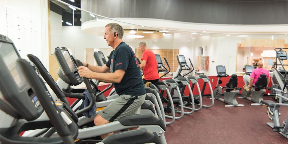 A community member exercises on an elliptical in the DeWitt Fitness Center.