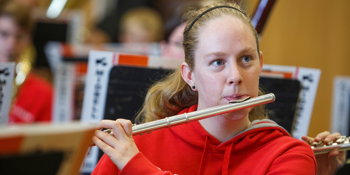 A flutist practices with the rest of the Symphonic Band during class.