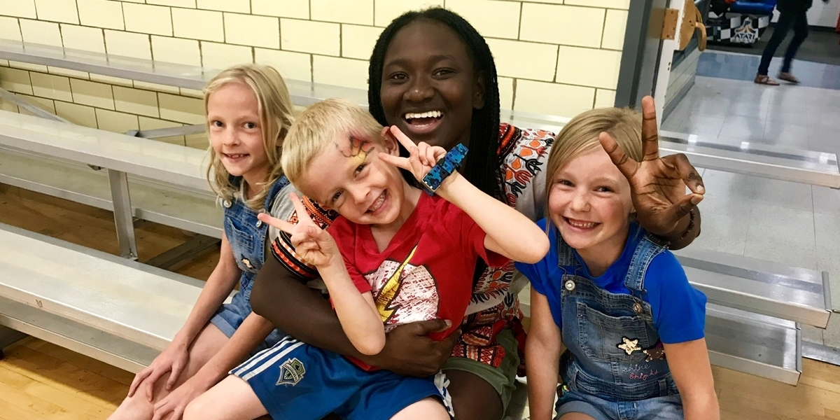 A Northwestern student poses with children during her Summer of Service.