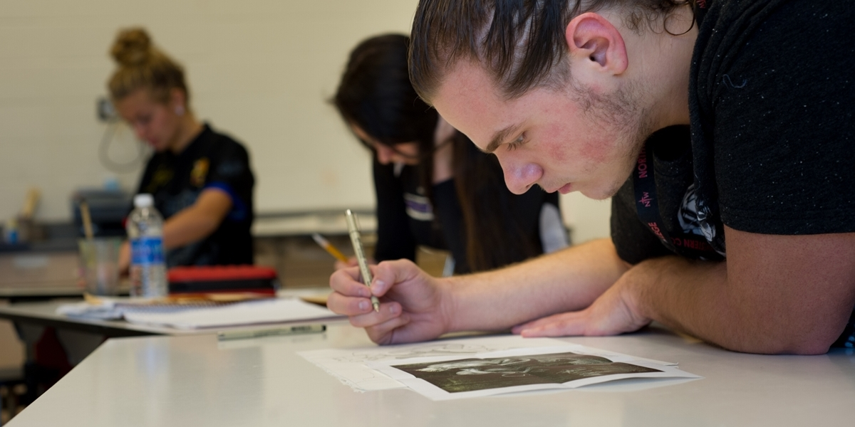 A Northwestern student works on a drawing during class.
