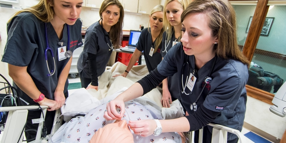 Northwestern nursing students administer medication to a patient simulator.