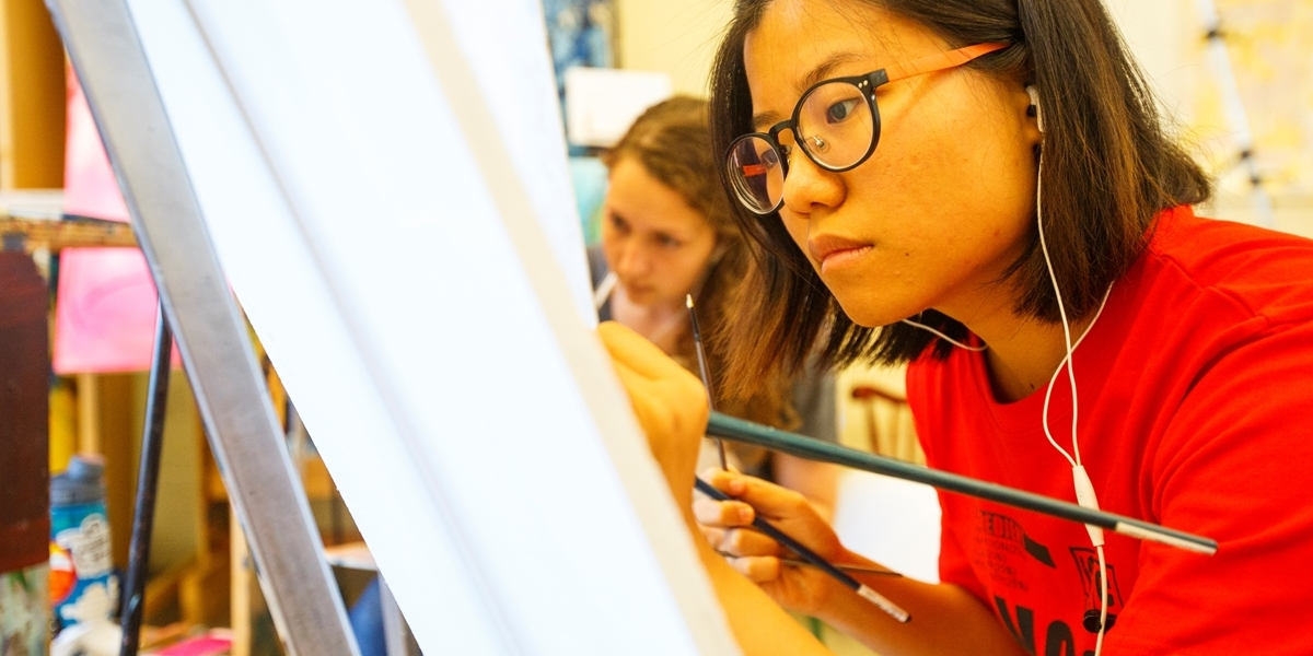 A Northwestern student works on a painting during class.